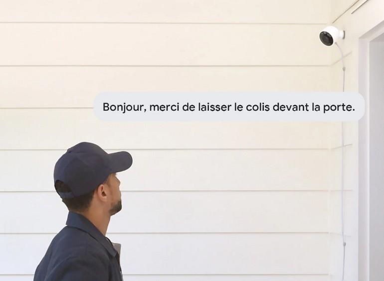 Google Nest Cam Outdoor fixé au-dessus d'une porte de maison avec un livreur au premier plan, visuel lifestyle