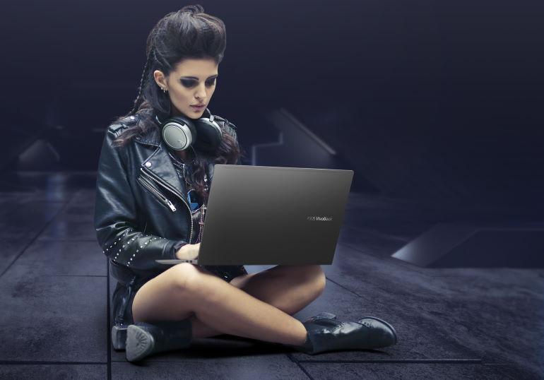 Une jeune femme assise en tailleur avec un PC portable Asus Vivobook sur les genoux