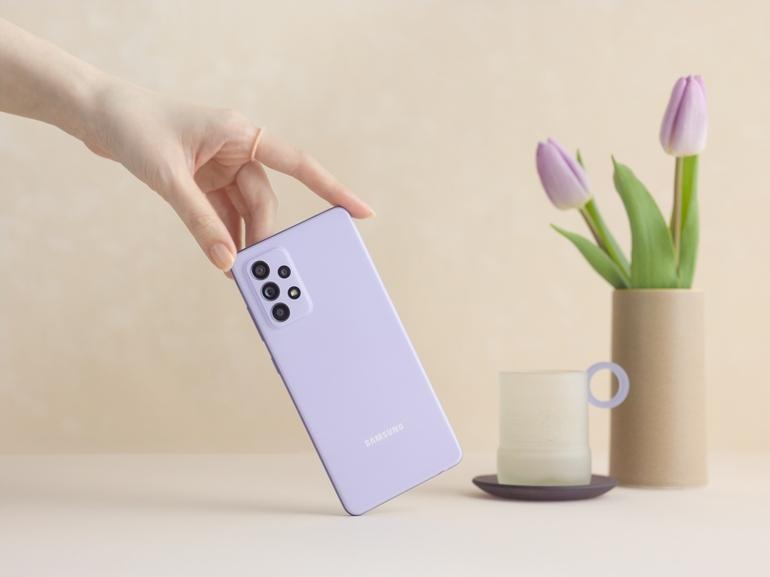Le smartphone Samsung Galaxy A52 en finition violet tenu par une main de femme dans un décor lifestyle