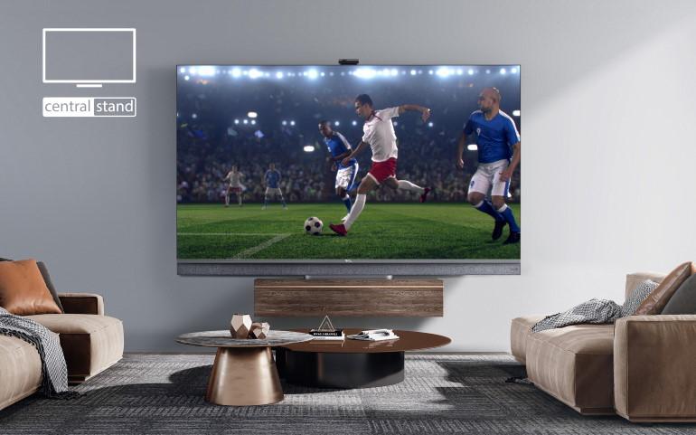 Un téléviseur TCL de la gamme C82 fixé à un mur dans un intérieur design. Le TV Mini LED affiche un match de football.